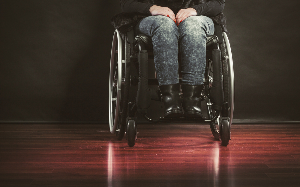 Front-facing view of a woman's legs in a manual wheelchair. She is wearing black stonewashed jeans and black boots, and is in a room with a dark wooden floor. You can only see her legs in the chair, no head or torso.