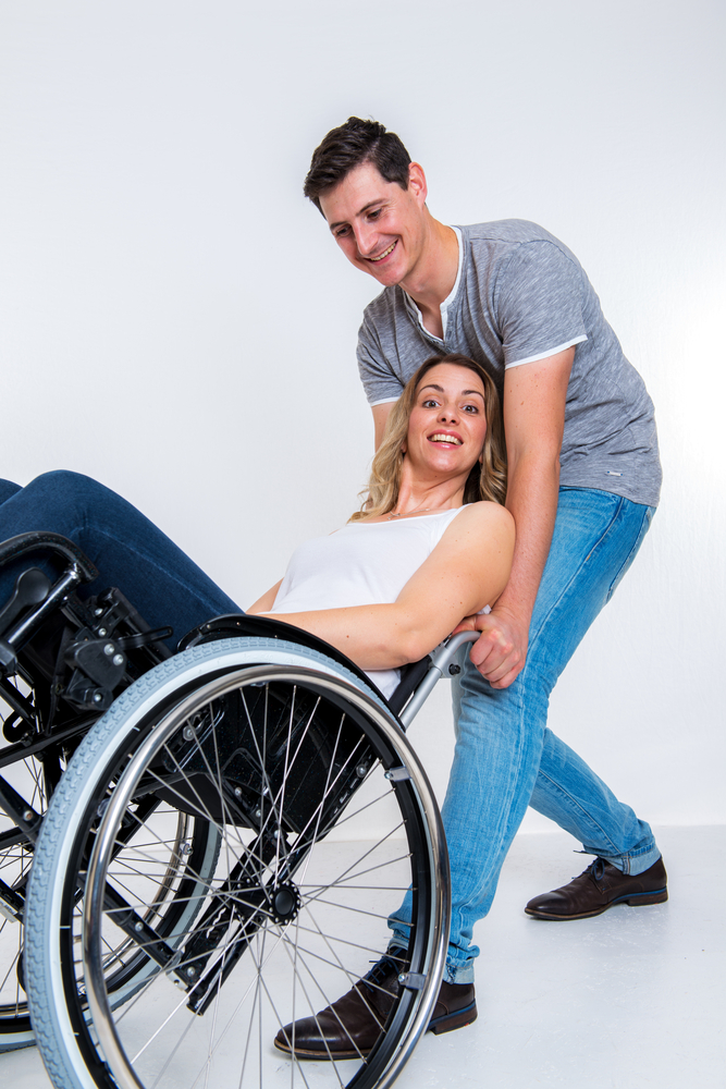 A white man with short brown hair in blue jeans and a gray t-shirt smiles at a blonde woman in a manual wheelchair as he tips her chair backwards from behind.