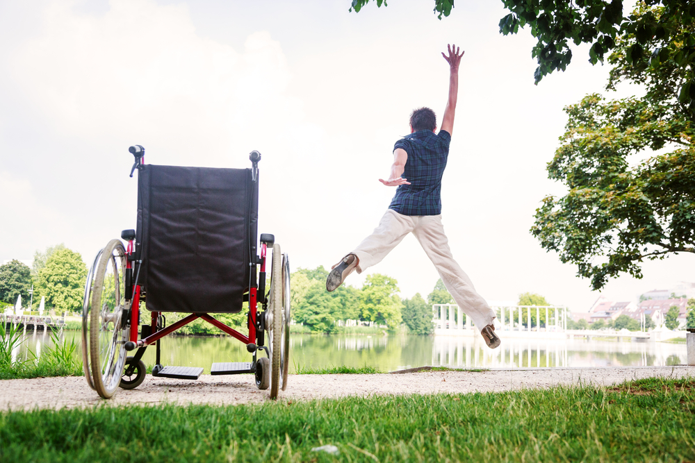 A woman with short brown hair in a blue short sleeved shirt and khaki pants leaps out of a manual wheelchair with her arms up in the air. There is a large pond in the background.