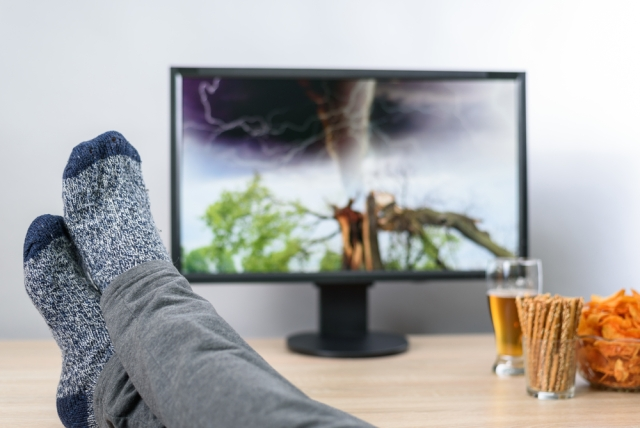 Person with legs resting on coffee table, watching a television showing an approaching tornado
