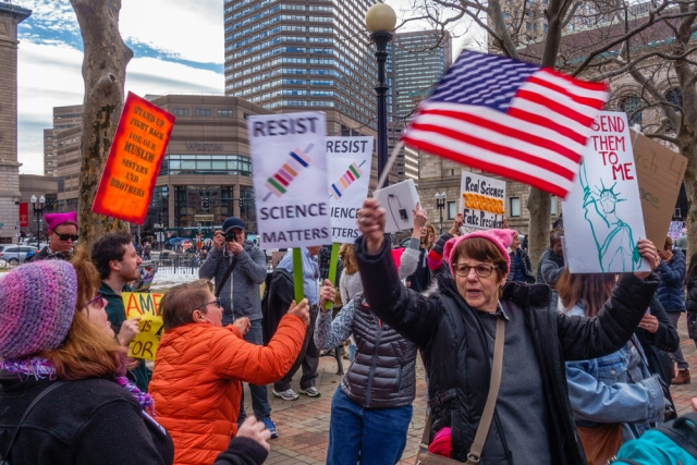 BOSTON, MA USA - FEBRUARY 19, 2017: Protesters hold up signs at the Stand Up for Science Rally in Copley Square Boston. Via Shutterstock.