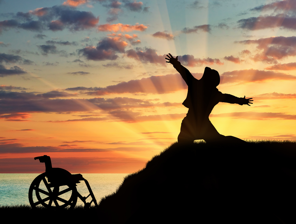 In silhouette against a sunset background, a person drops to their knees on a small hilltop and raises their arms out wide. Their manual wheelchair sits empty at the bottom of the hill.