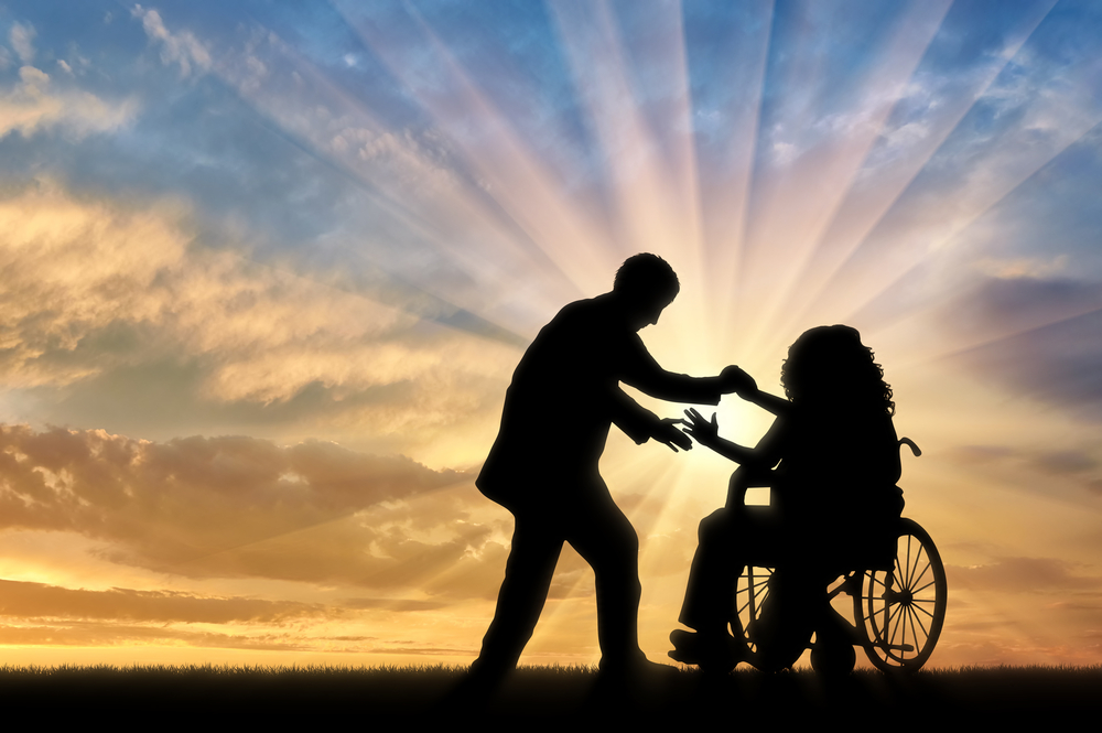 In silhouette against a sunset background, a man reaches out to take the hands of a woman in a manual wheelchair.