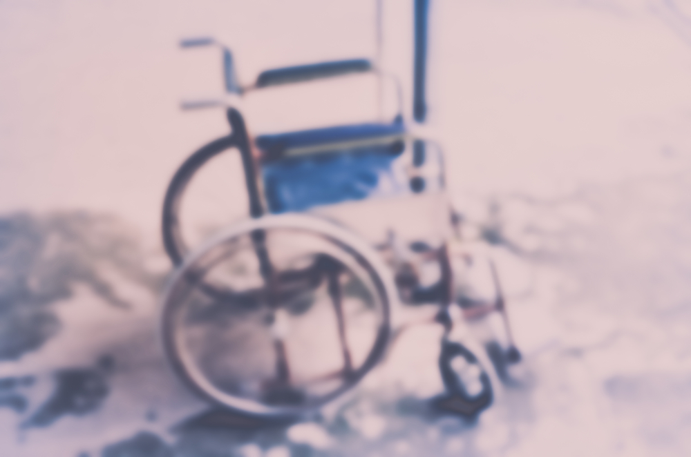 An out of focus manual wheelchair with a blue seat.