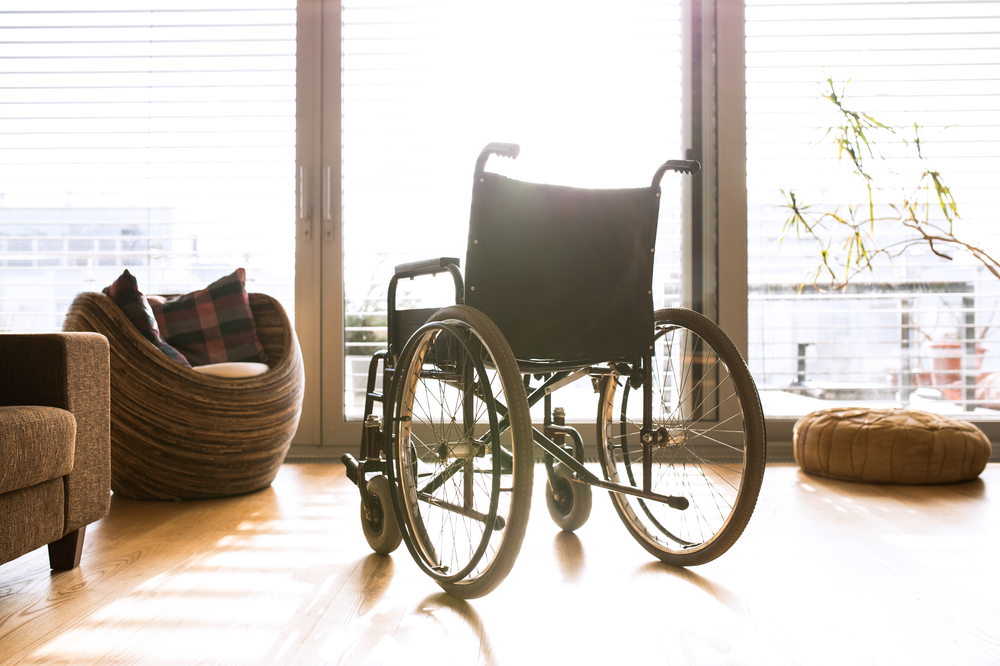 A black manual wheelchair sits facing a large window, with light streaming in over the chair from outside.