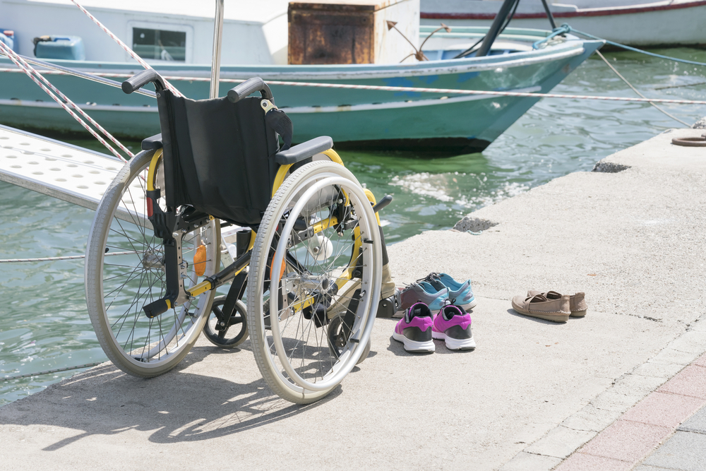 A manual wheelchair with a yellow frame, black seat, and gray tires sits unoccupied on a dock next to the water. Three pairs of shoes sit next to the chair. There are no people in the photo, only a boat in the background.