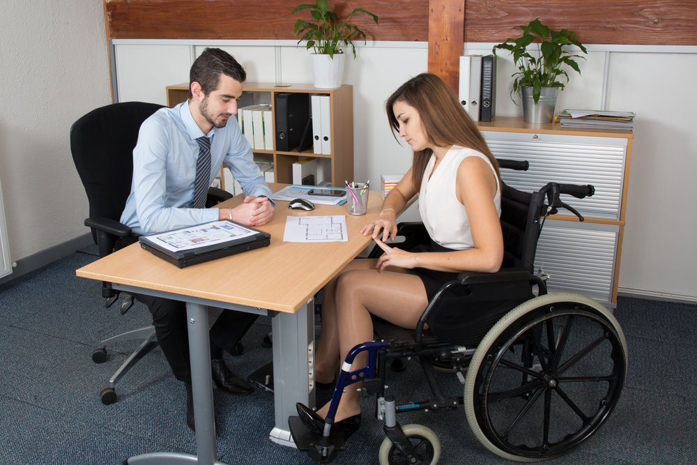 A young white man and woman, both with brown hair, sit on opposite sides of a wooden desk. The woman is in a manual wheelchair wearing a black skirt and a sleeveless white top. The man is in a light blue dress shirt and dark blue tie. There are binders and papers on the table between them.