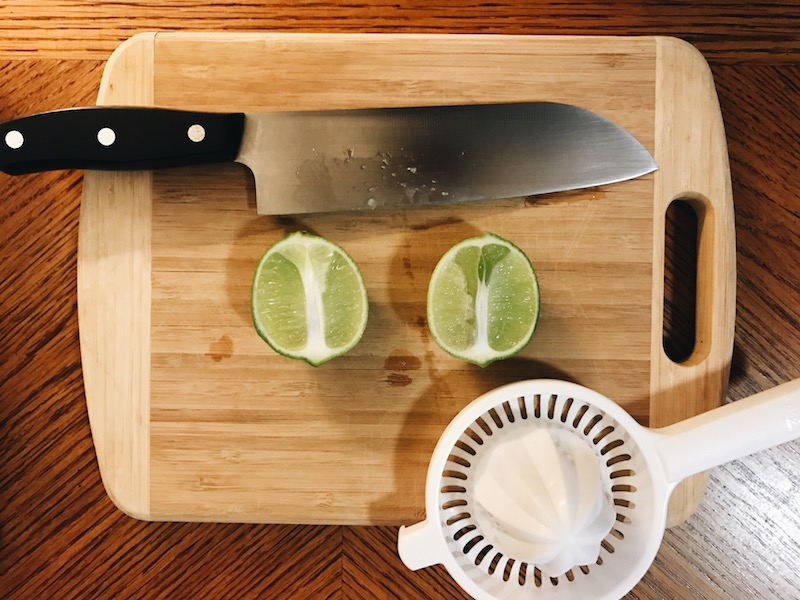 a lime, cut lengthwise, on a cutting board with a knife and a shitty juicer