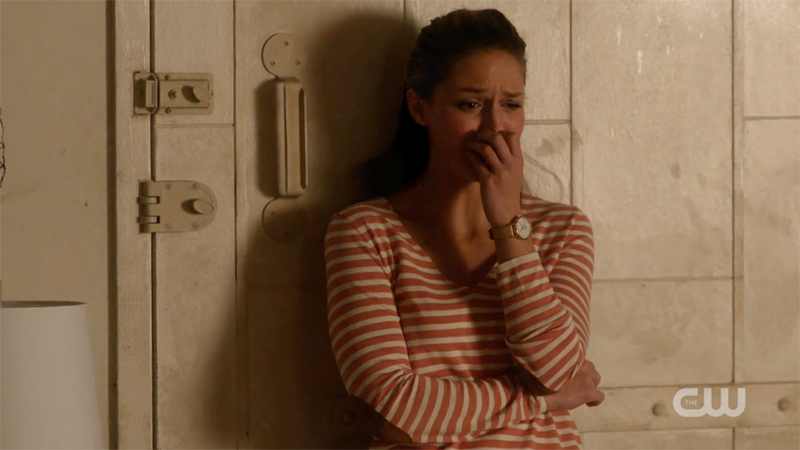 Kara cries, leaning against her door