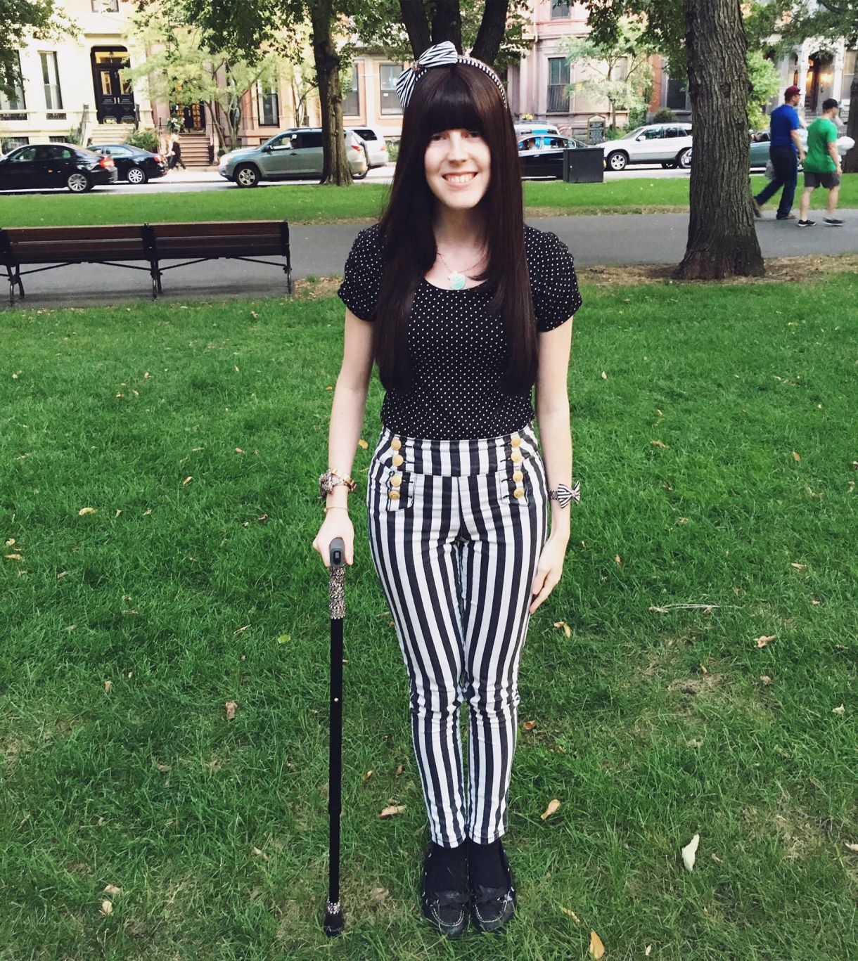 A white person in her twenties with long brown hair and blunt bangs stands on the grass in a park. She's holding a black cane and wearing black and white striped pants and a black top with small white polka dots, plus a headband with black and white stripes and a bow.
