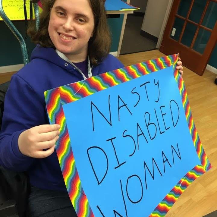 "A white woman in her mid twenties with brown hair and wearing a blue hoodie holds up a blue sign with a rainbow border that says ""Nasty Disabled Woman."""