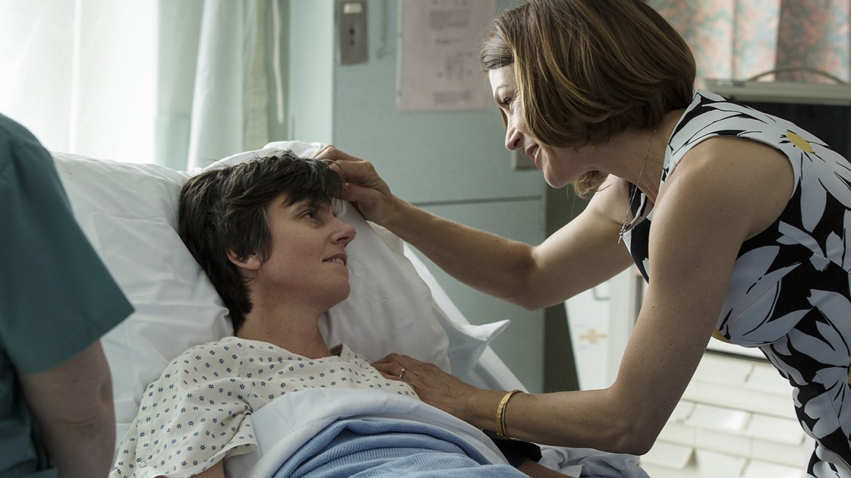 Tig, played by Tig Notaro, is in a hospital bed. A woman in a dress is touching her forehead lovingly.