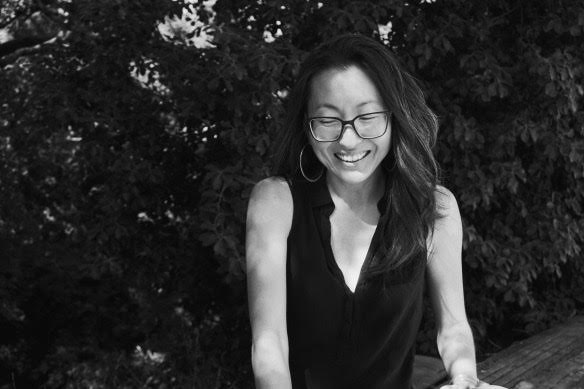 An Asian woman with long dark hair and square glasses smiles down toward the ground. The photo is in black and white, and she is wearing a sleeveless black top with a v-neck.