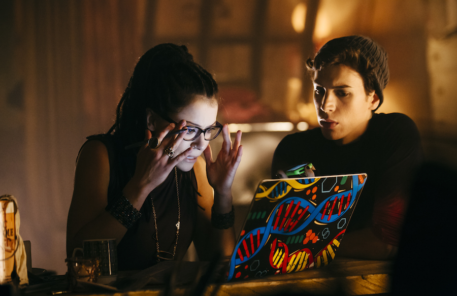 Image: Cosima, played by Tatiana Maslany, is looking at her laptop with her friend Felix, played by Jordan Gavaris. Cosima has, unfortunately for us all, dreadlocks. She is white and wearing glasses and seems shocked by what she sees on her laptop. Felix, next to her, is pensive and might not have a full view of the laptop. The back of the laptop is decorated with bright-colored DNA strands. It is nighttime.