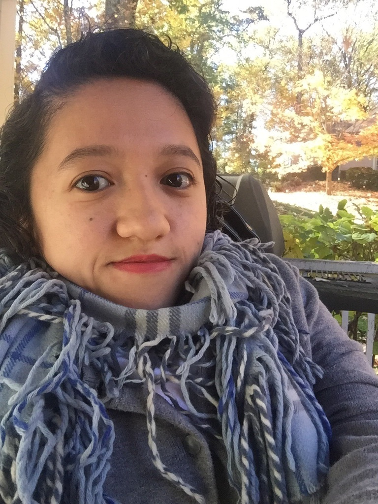An Asian woman in her late twenties sits outside in her electric wheelchair, looking at the camera. She has black hair and red lips and is wearing a gray plaid scarf with tasseled ends.