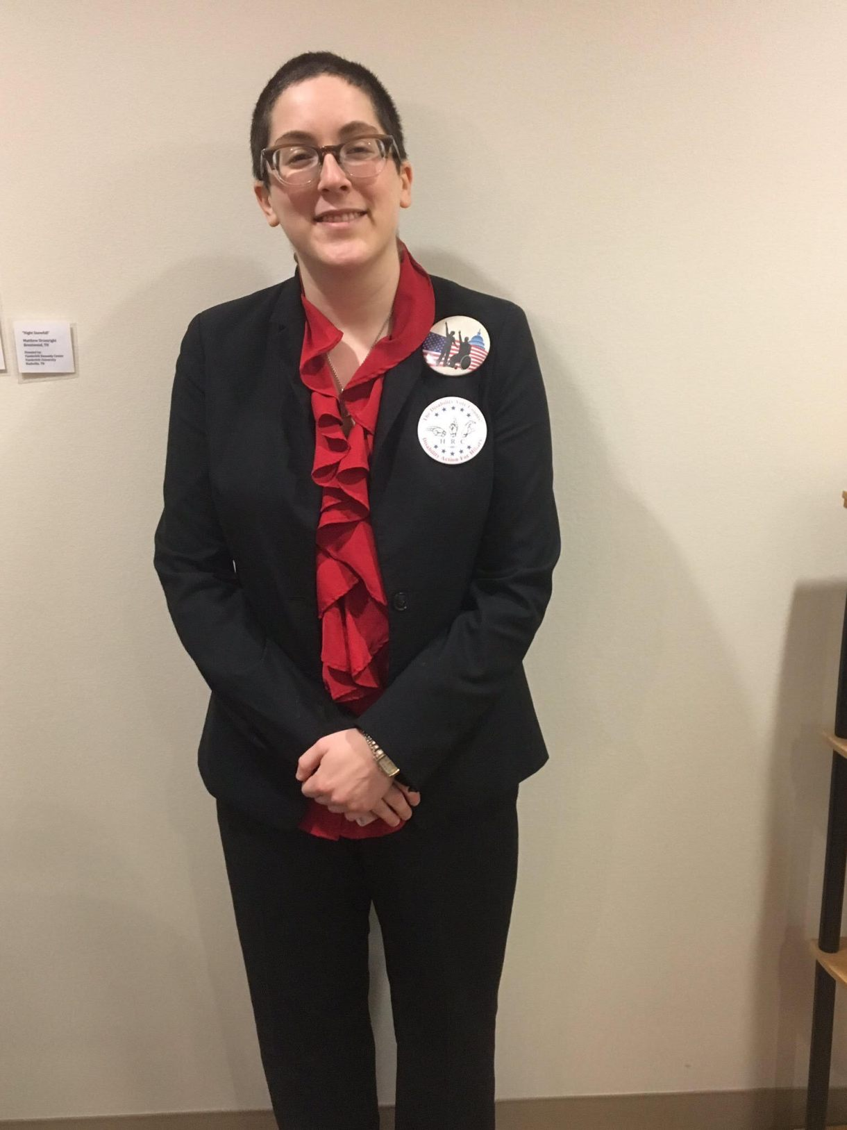 A white woman in her twenties with short brown hair stands with her arms folded at her waist against a white wall. She's wearing a black pantsuit with a red ruffled shirt underneath.