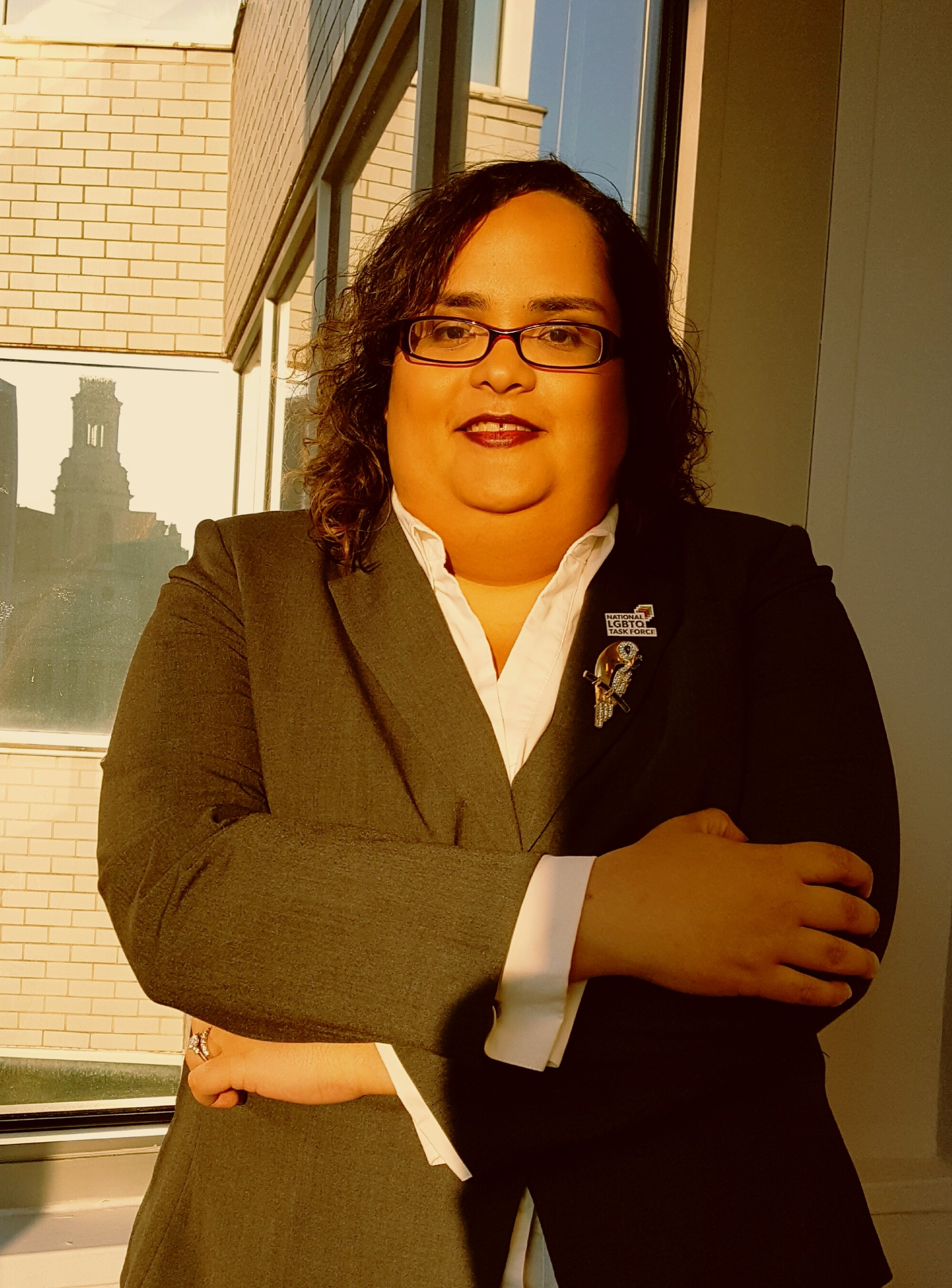 A Latina woman with square eyeglasses and red lips wearing a white shirt and black blazer stands with her arms crossed in front of a white brick building. The sun is lighting up her face and the right half of her body; her left arm is in shadow.