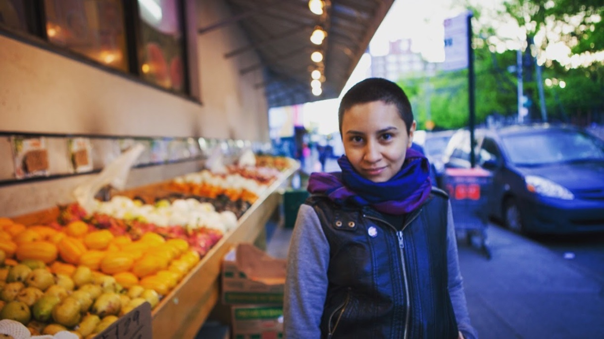 A person with a closely shaved head wearing a grey shirt, purple and blue infinity scarf, and black leather vest stands next to a sidewalk produce stand.