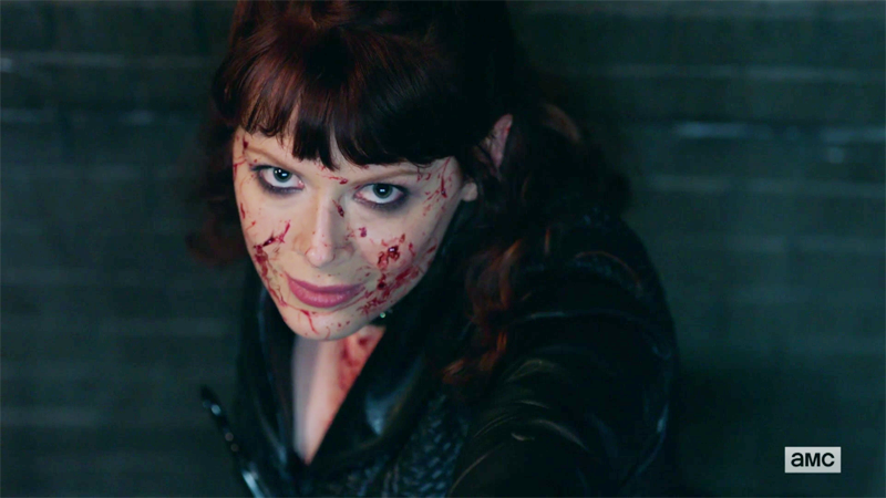 The widow smirks into the camera with blood all over her face