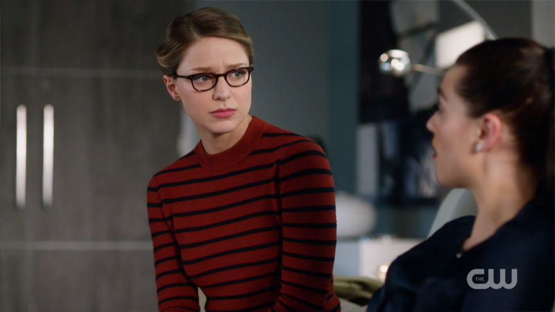 Kara sits on Lena's couch with a sympathetic look