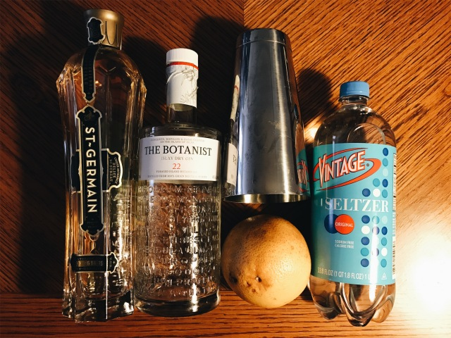 photo of ingredients: gin, seltzer, saint germain, a grapefruit and a Boston shaker