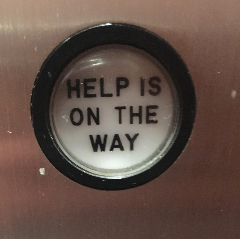 "An elevator button that says ""help is on the way"" in black block letters."