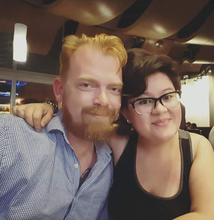 A young couple (a white man with red hair and a Latinx person with dark brown hair and glasses) smile at the camera with their arms around each other's shoulders.