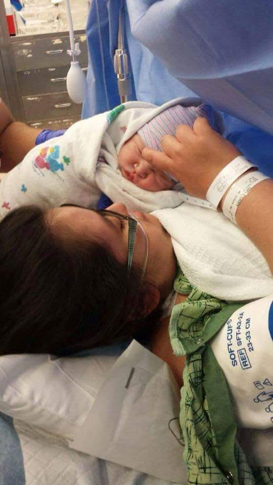A mother holds a newborn baby in their arms in a hospital bed.