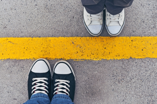 An overhead view of two pairs of feet in sneakers, each standing on either side of a thick yellow line.