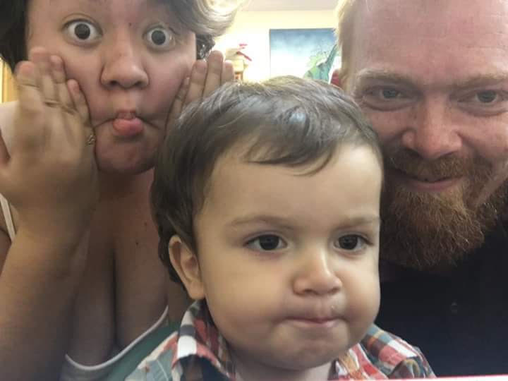 A family of three, two parents and their young child, smile into the camera. The mom, who's on the left side of the frame, is making a fish face.