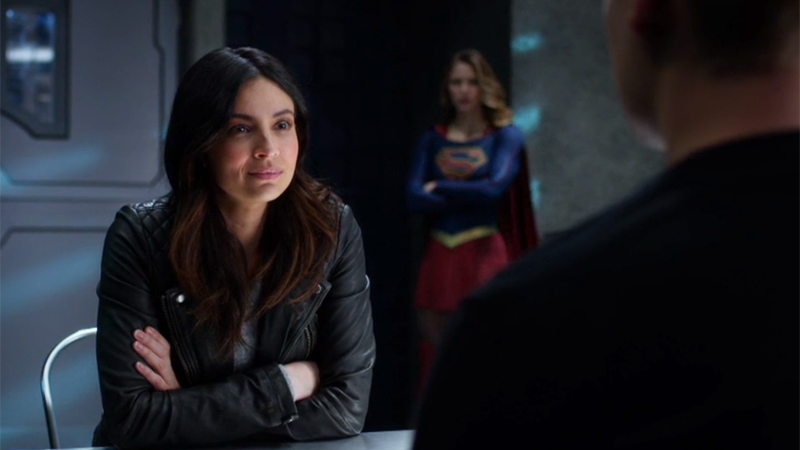 Maggie sits at the table, Supergirl stands watch behind her