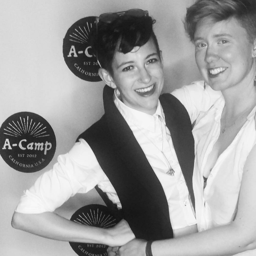 Two women in formal wear pose with their arms around each other and smile for the camera in front of an A-Camp branded backdrop.