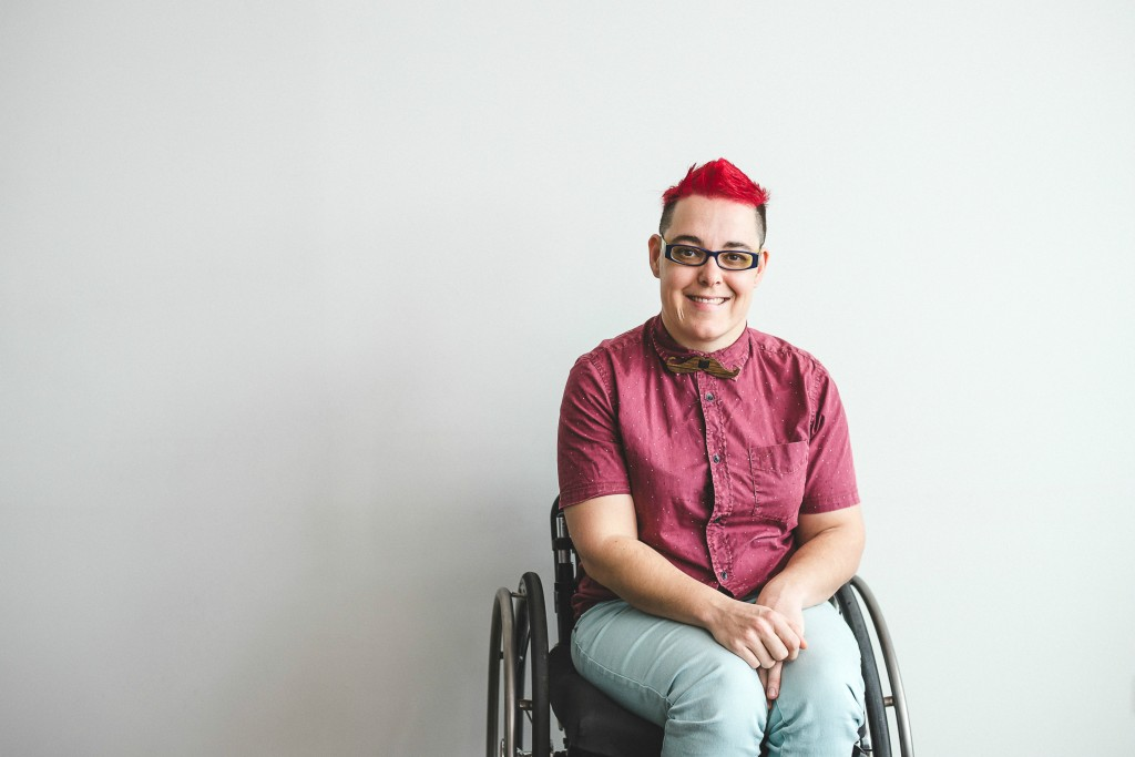 A woman with a red mohawk wearing jeans and a reed shirt sits in her wheelchair against a blank wall, smiling.