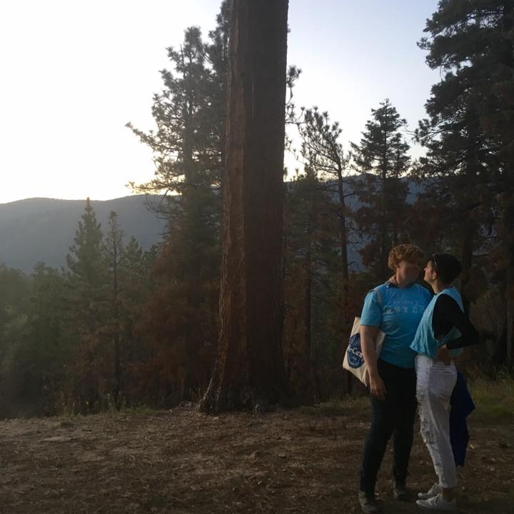 Two women look lovingly at each other while standing on a wooded mountaintop. They are both wearing light blue shirts, and one is carrying an A-Camp tote bag.