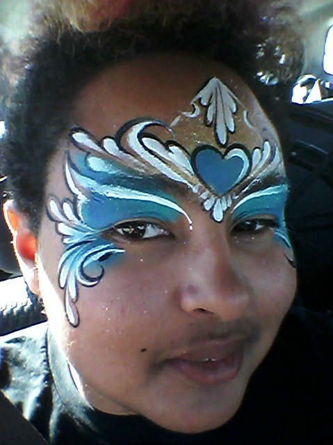 A young person with brown skin and dark hair looks into the camera. Their face is painted blue and white over the eyes, with a heart in the center of their forehead.