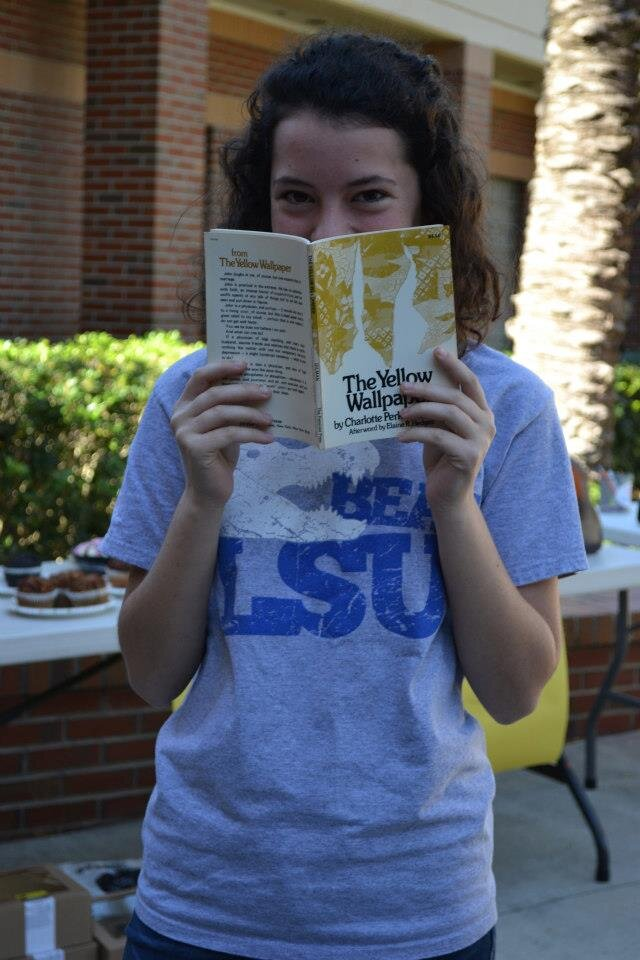 A young white woman with curly brown hair smiles from behind the book The Yellow Wallpaper.