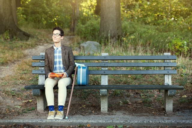 A dapper-looking person with a wooden cane sits at the end of a park bench.