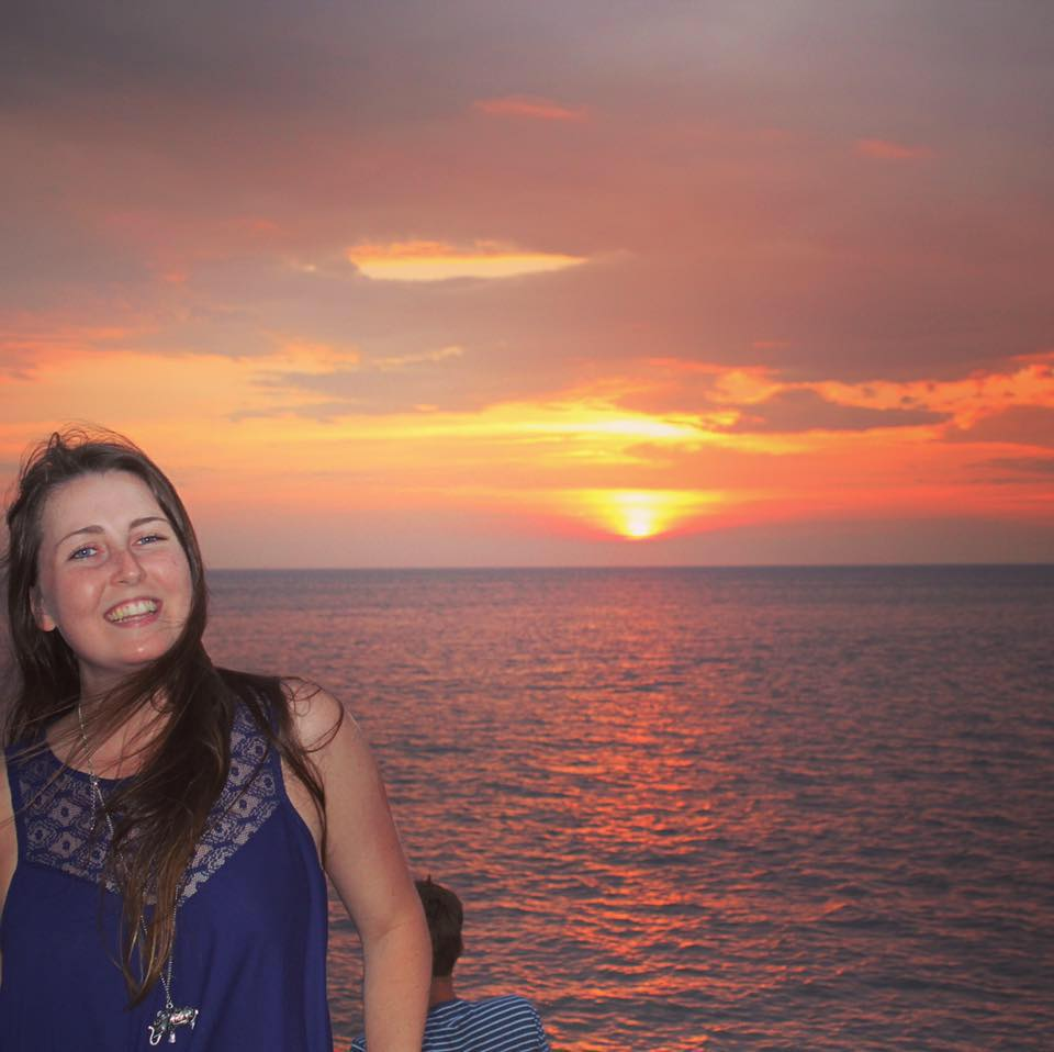 A young white woman with long brown hair smiles in front of a sunset over the ocean.