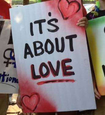"A spray-painted sign that says ""It's about Love"" from a marriage rally."