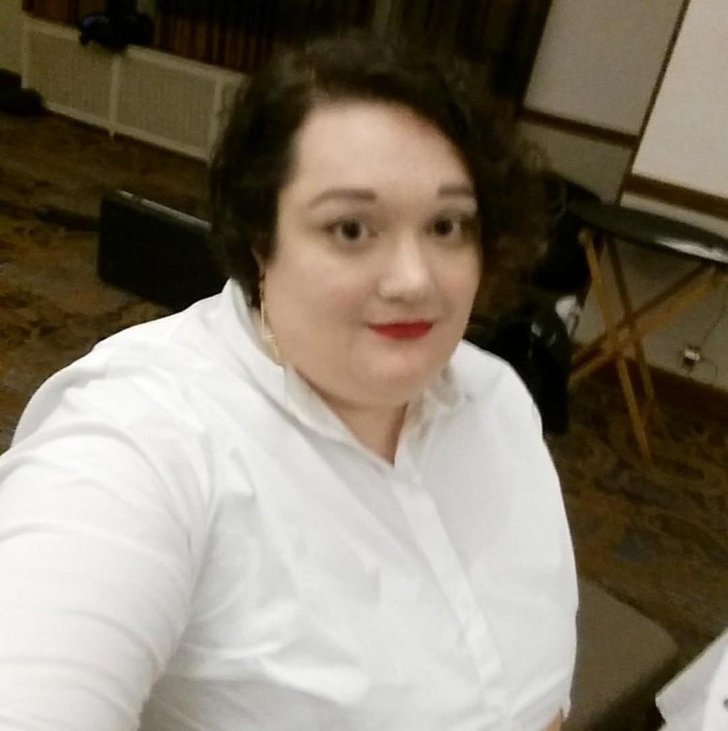 A woman wearing red lipstick and a white button down shirt takes a selfie.