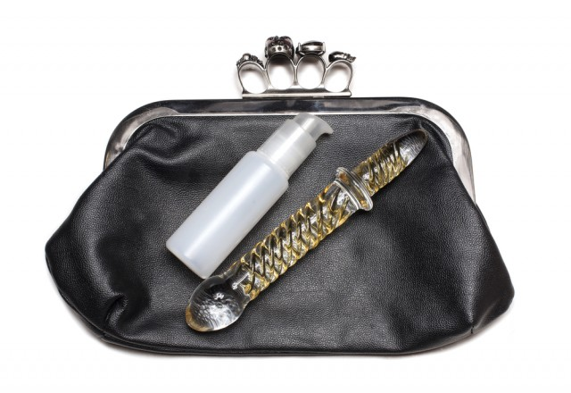 a glass dildo and bottle of lube in a nice clutch purse