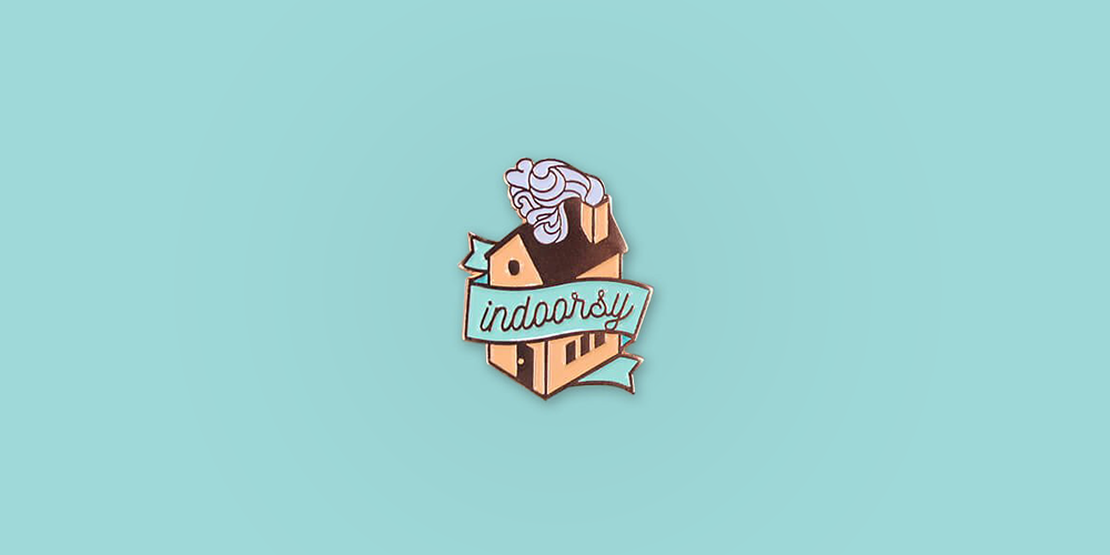 "Indoorsy Enamel Pin / Description: House with swirly smoking chimney, banner across the front reads ""Indoorsy"" / Metal: Rose Gold / Enamel Colors: Coral and Mint"