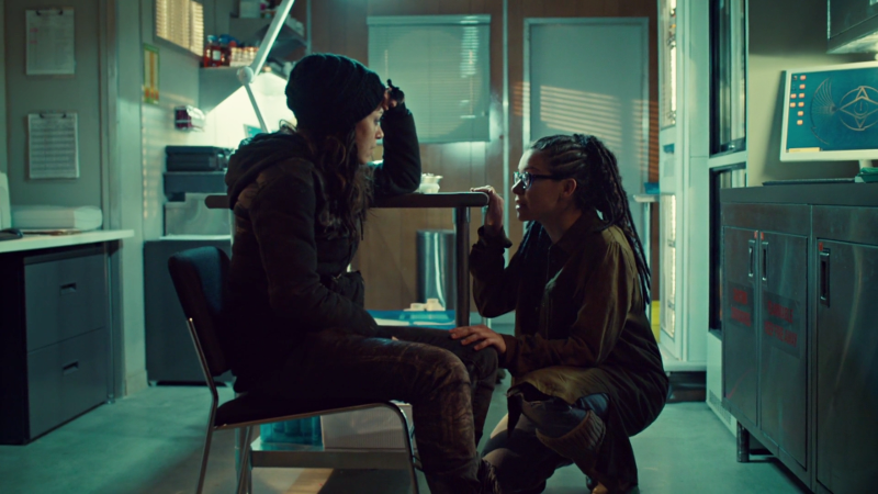 Sarah sits and Cosima crouches in front of her to talk