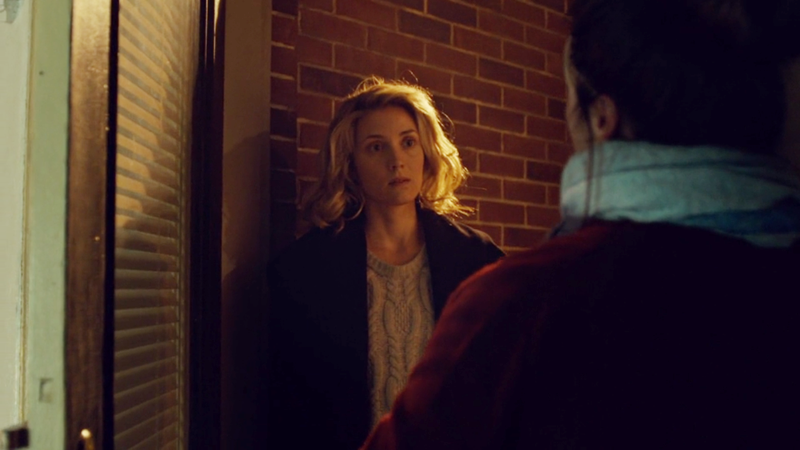 Delphine stands in the doorway, basking in the porchlight like an angel