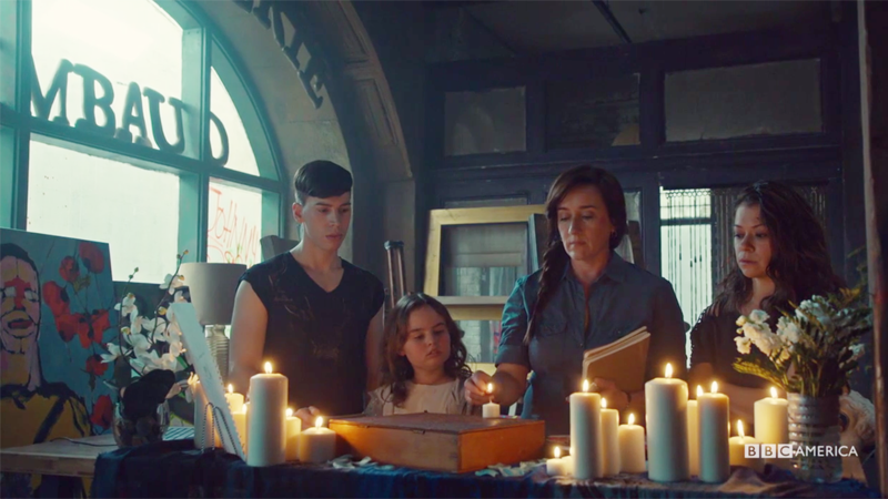 Mrs. S, Felix, Sarah and Kira stand around candles and MK's mask