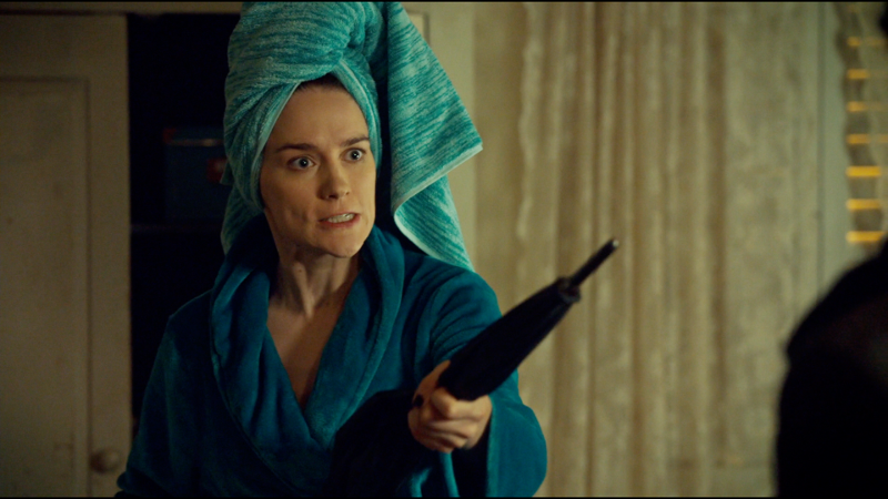 Wynonna with her hair up in a towel wields an umbrella as a weapon
