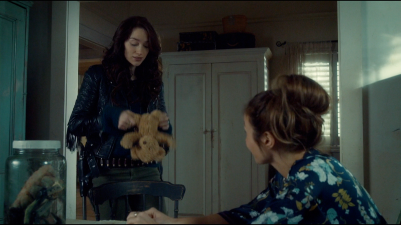 Wynonna holds a teddy bear at an awkward spread eagle type position