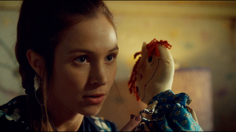 Waverly holds up a lighter and a creepy doll, ready to party