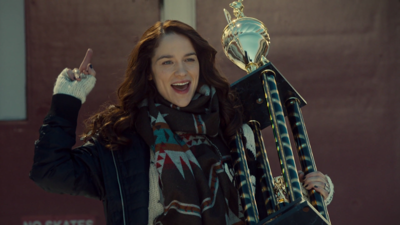 Wynonna does a victory walk out of the school with her trophy and her middle finger high in the air