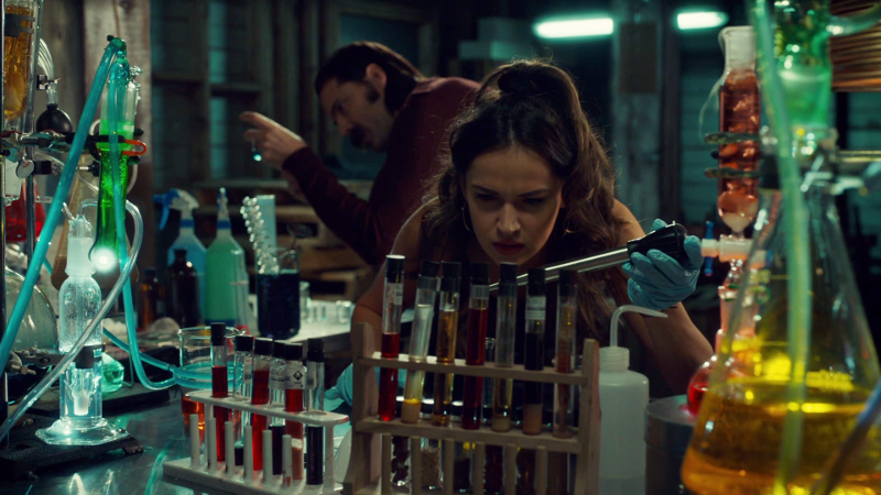 Rosita is holding a turkey baster looking thing over some vials in their little lab